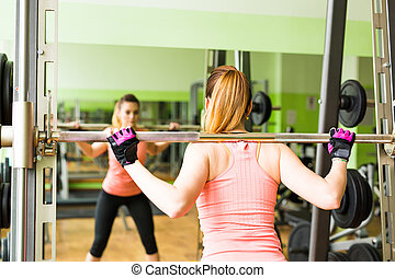 Young woman exercising with barbell in gym