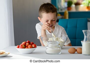 Child mixing white cottage cheese in a bowl - 7 year old boy...