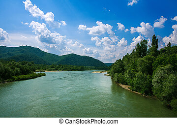 River in mountain valley in woods on blue sky background -...