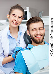 Portrait of a female dentist and young man in a dentist...
