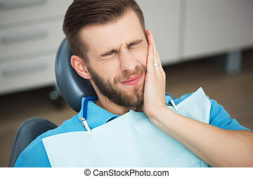 Portrait of young man with tooth pain sitting in a dentist's...
