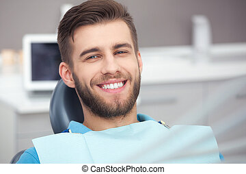 Portrait of happy patient in dental chair. - My smile is...
