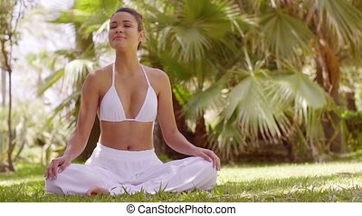Young woman meditating in a tropical garden - Young woman...