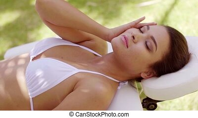 Relaxed young woman lying on a spa bed - Relaxed young woman...