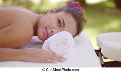 Gorgeous young woman having a spa treatment lying naked on a...