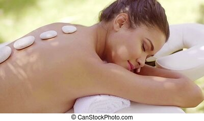 Woman having a hot stone spa massage with a close up view of...