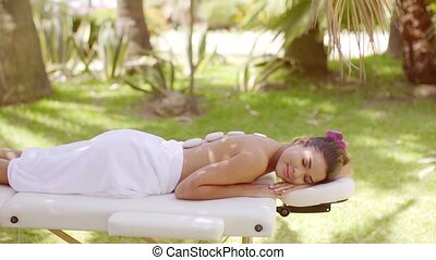 Pretty young woman enjoying a hot stone massage at a summer...