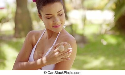 Happy woman using exfoliating brush on skin - Happy...