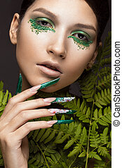 Beautiful girl with art make-up, fern leaves and long nails....