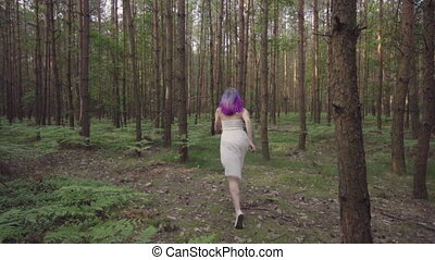 Woman in dress running in forest