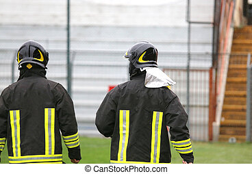 two helmeted firemen for the security service in the stadium...