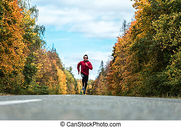 Man runs on the road - Man in a sports uniform and glasses...