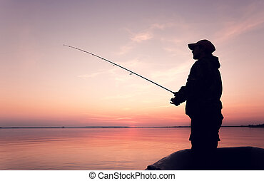 Silhouette man in a boat with a fishing rod - Silhouette of...