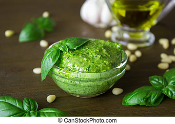 Homemade pesto sauce with ingredients over wooden table.