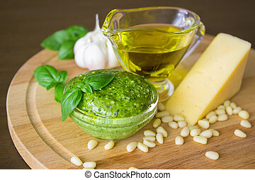 Homemade pesto sauce with ingredients over old table.