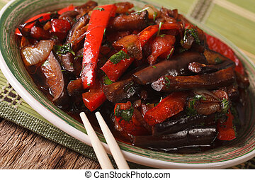 Eggplants fried with vegetables in a Korean-style close-up....