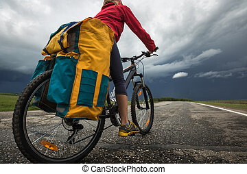 Lady hiker riding loaded bicycle on the paved asphalt road...