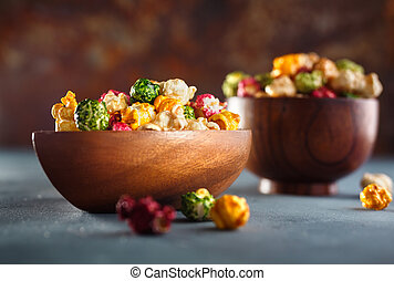Fruit flavored popcorn in wooden bowl. - Colored popcorn....
