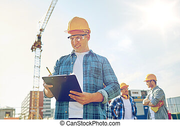 builder in hardhat with clipboard at construction -...
