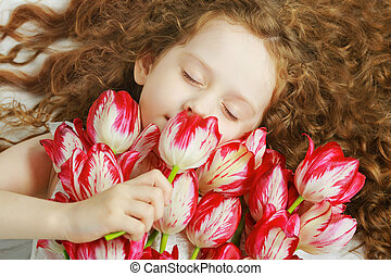 Girl smelling a bouquet of tulips - Curly Girl enjoying the...