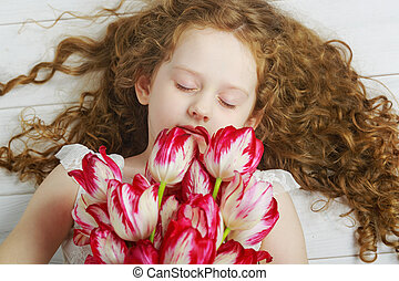 Curly Girl enjoying the smell of tulips closed her eyes