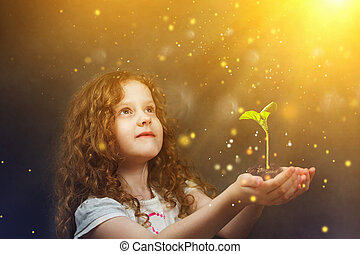 Little girl holding young green plant in sunlight. Ecology concept.