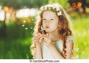 Beautiful young child on white dress blowing a dandelion in...