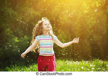 Little curly girl enjoy flying dandelion in sunset light....