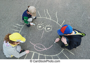 Children is drawing sun on asphalt in spring park