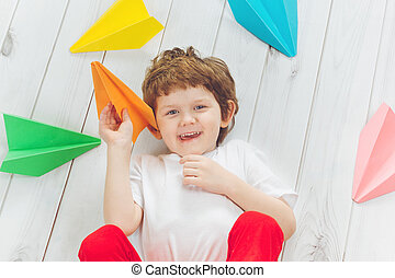 Happy laughing child throwing paper airplane indoors. Happy...