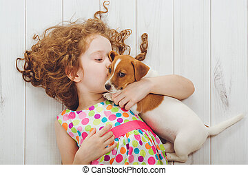 Little girl and her puppy whispers on wood background.. -...