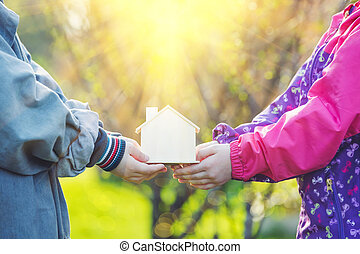 Children hold toy house in hands