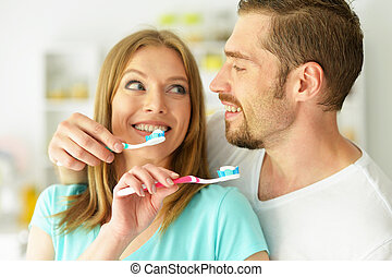 Young couple brushing their teeth