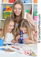 mother with her daughters doing homework - portrait of happy...