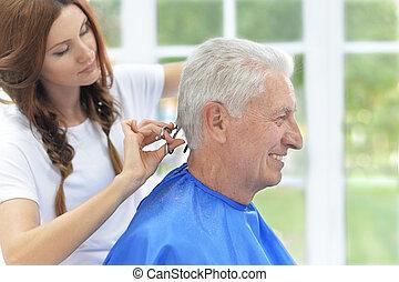 Man having a haircut from hairdresser - Man having a haircut...