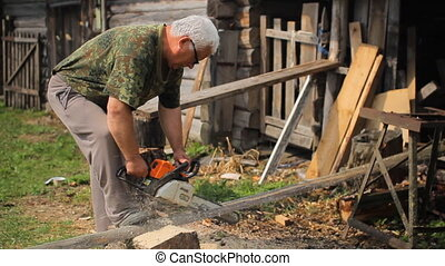 A man is cutting some wood using a chainsaw