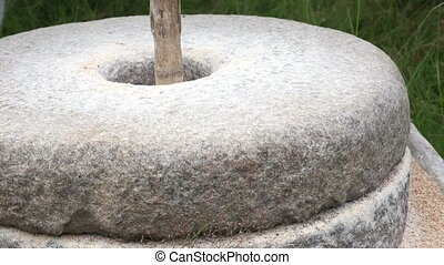 Historic hand-driven millstone - Close-up shot of man grinds...