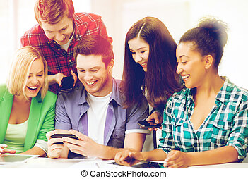 students looking at smartphone at school - education,...