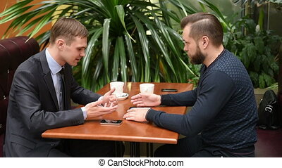 Two men look after the passing woman sitting in cafe - Two...