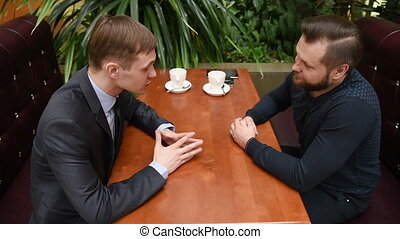 Handsome two businessmen have a meeting in cafe. tense men -...