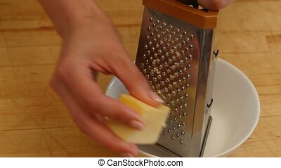 Woman rubs cheese grater. 4k - Woman rubs cheese grater in...