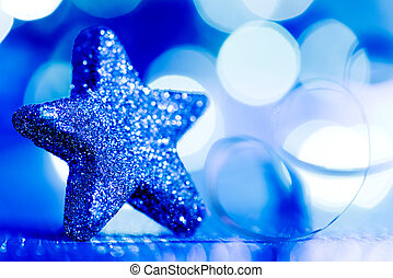 Blue Christmas star and glitter on the blue background