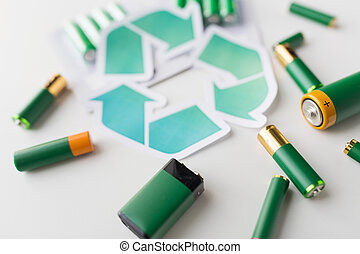 close up of batteries and green recycling symbol - waste...