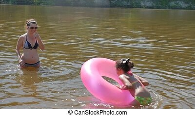 teen girl and mother floating river vacation rubber disc...
