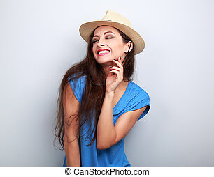 Happy casual toothy laughing woman in summer hat on blue...