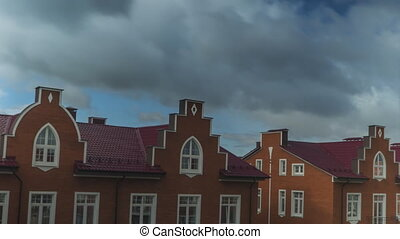 Smooth time lapse of clouds flying over red brick town...