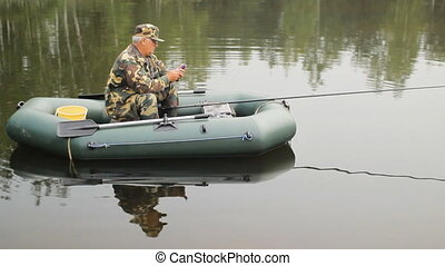 The man calling by phone on the lake. A fisherman with a fishing rod on the inflatable boat