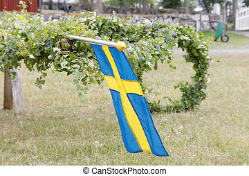 Maypole with leaf and swedish flag before raising it -...