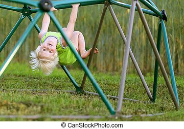 Little Child Playing at PLayground Climbing on Monkey Bars -...