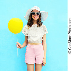 Fashion pretty woman in straw hat with air balloon over...